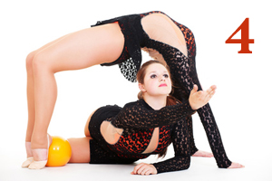 two gymnasts posing with yellow ball